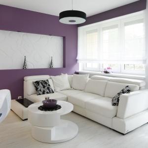 Kolory bieli oraz ecru zdominowały przestrzeń salonu. Ciekawy kontrast stanowi kolor wrzosowy zastosowany na fragmentach ścian. Projekt: Joanna Ochota. Fot. Bartosz Jarosz