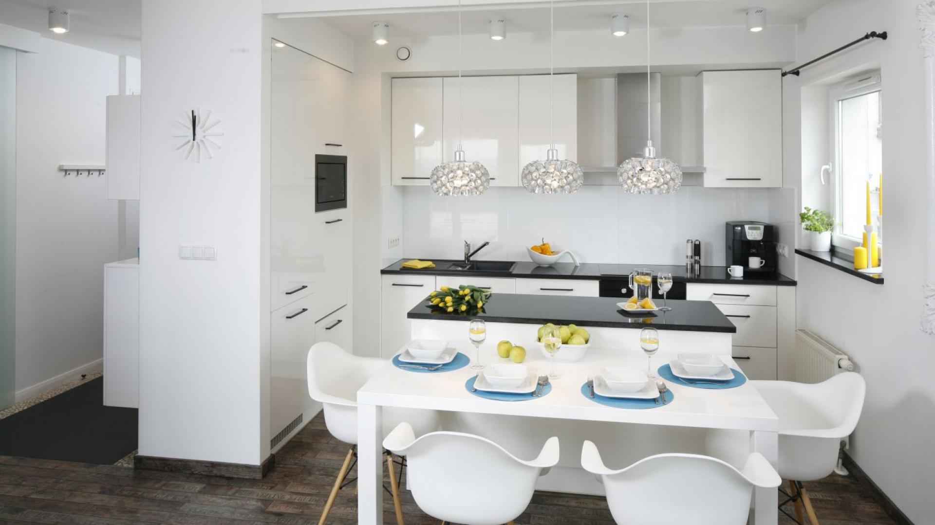 Białe meble kuchenne z frontami na wysoki połysk odbijają światło i otoczenie. Projekt: Katarzyna Uszok. Fot. Bartosz Jarosz