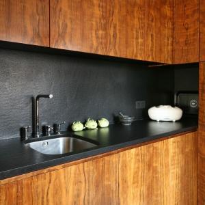 Kuchnię urządzono w klimacie amerykańskiego minimalizmu z lat 50. Drewno połączono z czernią, w której wykończono blat i ścianę nad nim. Obie powierzchnie są pokryte konglomeratem. Projekt: Kasia i Michał Dudko. Fot. Bartosz Jarosz