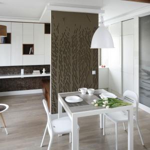 Stół jadalniany i harmonizujące z nim kolorem i materiałem krzesła ustawiono w przedpokoju. Odrębność strefy spożywania posiłków zaznaczono dekoracyjnym panelem na ścianie. Projekt: Małgorzata Mazur. Fot. Bartosz Jarosz