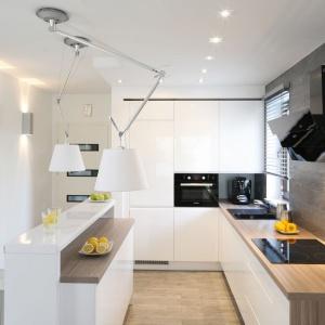 Biała zabudowa kuchenna poprowadzona pod sam sufit sąsiaduje ze ścianą wykończona płytkami w popielato-szarym kolorze. Projekt: Karolina Stanek-Szadujko, Łukasz Szadujko. Fot. Bartosz Jarosz