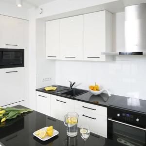 W białej kuchni czarny blat wyróżnia się na tle zabudowy oraz ściany nad blatem, zwieńczonej mlecznym szkłem. Projekt: Katarzyna Uszok. Fot. Bartosz Jarosz