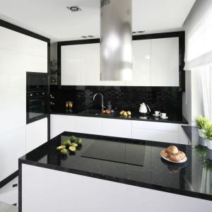 Zabudowa kuchenna ma połyskujące białe fronty oraz efektowne czarne ramy, z którymi idealnie koresponduje czarny blat. Projekt: Katarzyna Mikulska-Sękalska. Fot. Bartosz Jarosz
