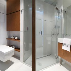 Kabina na posadzce oraz lekkie formy zabudowy dodają optycznej przestrzeni małej łazience. Projekt: Anna Maria Sokołowska. Fot. Bartosz Jarosz