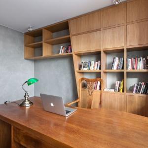 Oryginalna zabudowa zestawia zamknięte i otwarte półki z geometrią i asymetrycznymi podziałami. Efekt to bardzo nowoczesna biblioteczka w równie nowoczesnym mieszkaniu. Projekt: mode:lina Architekci. Fot. Marcin Ratajczak