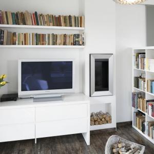 W mieszkaniu są dwie sąsiadujące ze sobą biblioteczki. Jedna zamyka salon od strony holu i kuchni, druga to dwie proste półki nad strefą TV. Projekt: Katarzyna Uszok. Fot. Bartosz Jarosz