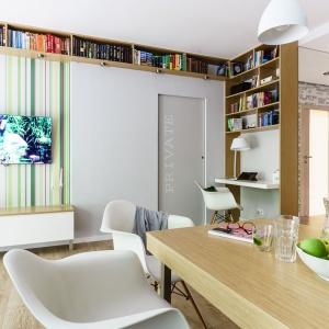 Ciekawe rozwiązanie architektoniczne. Pod sufitem poprowadzono rząd otwarych półek na książki, który przechodzi w dół wzdłuż półscianki działowej, przy której urządzono również kącik do pracy czy (oczywiście) relaksu przy książce. Projekt: Joanna Morkowska-Saj. Fot. foto & mohito