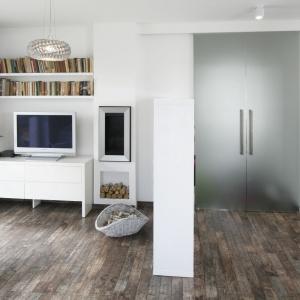 W tym mieszkaniu przestrzeń podzielono między innymi za pomocą... biblioteczki na książki, która zamyka strefę z TV od strony przedpokoju. Projekt: Katarzyna Uszok. Fot. Bartosz Jarosz