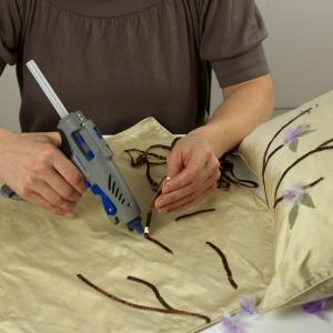 Krok 3  Za pomocą pistoletu do klejenia Dremel Glue Gun przyklej taśmę z cekinami do poszewki, aby powstały gałązki. Przemyśl wcześniej wzór, jeśli chcesz go powtórzyć na kilku poduszkach. Fot. Dremel