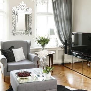 Na ścianie pomiędzy oknami wisi piękne lustro w zdobnej, srebrzystej ramie, wpisujące się w klasycyzującą aranżację wnętrza. Z kolei szafka RTV w całości pokryta lustrzaną taflą jest niemal niewidoczna. Projekt: Iwona Kurkowska. Fot. Bartosz Jarosz