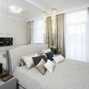 Aranżację wnętrza sypialni utrzymano w stylu glamour, pełnym blasku i przepychu. Na ścianie za wezgłowiem łóżko zamontowano ogromne lustro, ozdobione ciekawym wzorem geometrycznym. Projekt: Karolina Łuczyńska. Fot. Bartosz Jarosz