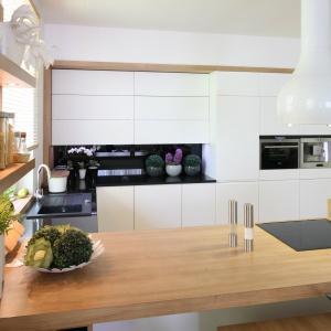 Wysoka zabudowa kuchenna została obramowana drewnianą oprawą, a fronty kuchenny wykończone są w macie. Matowe powierzchnie przełamano połyskującym czarnym lacobelem nad blatem. Projekt: Małgorzata Błaszczak. Fot. Bartosz Jarosz