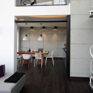 W tym salonie w stylu loft betonowe płyty pokrywają wysoką na dwie kondygnacje ścianę, a także ścianę w widocznej w tle jadalni połączonej z kuchnią. Projekt: Justyna Smolec. Fot. Bartosz Jarosz