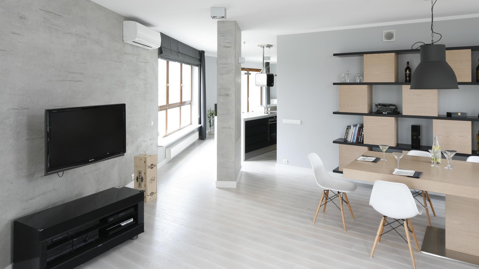 Na ścianie za TV oraz dalej, na kolumnie sąsiadującej z kuchnią położono betonową strukturę, która podkreśla surowy charakter minimalistycznej aranżacji salonu. Projekt: Maciejka Peszyńska-Drews. Fot. Bartosz Jarosz