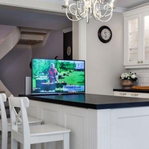 W tej kuchni urządzonej w klasycznym stylu w zabudowie schowano nowoczesne rozwiązania. Jednym z nich jest telewizor chowany w blacie wyspy kuchennej. Projekt: Małgorzata Błaszczak. Fot. Pracownia Mebli Vigo