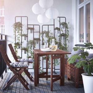 Metalowy kwietnik na jednej ze ścian z miejscem na zawieszenie licznych doniczek pozwala stworzyć porośniętą kwiatami ścianę i sam w sobie intryguje swoją formą. Fot. IKEA