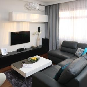 Ciemna, szara kanapa łączy achromatyczne barwy zastosowane w aranżacji salonu. Projekt: Anna Maria Sokołowska. Fot. Bartosz Jarosz