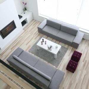 Szare kanapy oraz dywan wyglądają efektownie na tle drewnianej podłogi. Projekt: Karolina i Artur Urban. Fot. Bartosz Jarosz