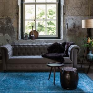 Elegancki dywan o błękitnej barwie ożywia wnętrze urządzone w stylu vintage. Fot. NS Home