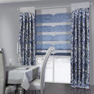 Roleta i towarzyszące jej zasłony zdobią wzory w różnych odcieniach koloru niebieskiego. Fot. Eurofirany