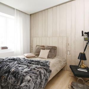 Ścianę za łóżkiem wykończono taką samą tapicerowaną tkaniną, jak wezgłowie mebla. Obie powierzchnie się niemal ze sobą scalają w jedną całość. Projekt: Małgorzata Muc, Joanna Scott. Fot. Bartosz Jarosz