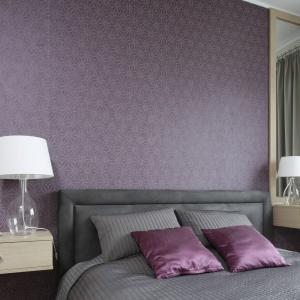 Ścianę w sypialni wykończono tapetą w śliwkowym kolorze z delikatnym, geometrycznym wzorem. Projekt: Joanna Morkowska-Saj. Fot. Bartosz Jarosz