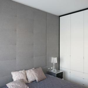 Szara miękka ściana pokryta tapicerowaną tkaniną jest przedłużeniem zagłówka nad łóżkiem w sypialni. Projekt: Anna Maria Sokołowska. Fot. Bartosz Jarosz