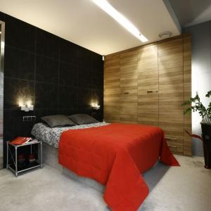 Ścianę za łóżkiem wykończono dużymi kwadratowymi płytkami w czarnej barwie z subtelnym, dekoracyjnym wzorem. Projekt: Liliana Masewicz-Kowalska. Fot. Marcin Onufryjuk