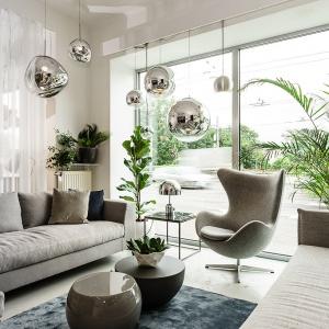 Liczne podwieszane srebrzyste kule i formy kulo-podobne stanowią oświetlenie w tym eleganckim szarym salonie.  Fot. Mesmetric Concept Store