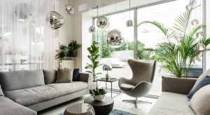 Oświetlenie w salonie może przybrać różne formy - od dekoracyjnych lamp po dyskretne reflektory w podwieszanym suficie.