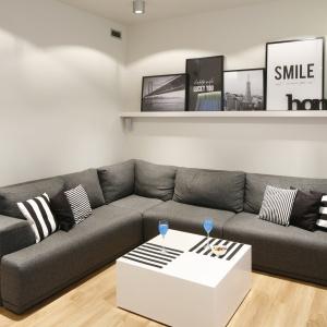Białe ściane i czarno-białe dodatki w skandynawskim stylu świetnie komponują się z ciemnoszarym narożnikiem i białym stolikiem kawowym. Projekt: Katarzyna Uszok. Fot. Bartosz Jarosz