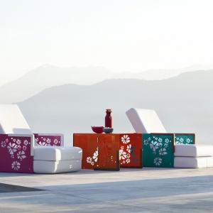 Wielofunkcyjny mebel ogrodowy Kube, mogący pełnić – w zależności od sposobu, w jaki go złożymy/rozłożymy - funkcję fotela, leżaka, pufa lub stolika pod laptop. Winylowy, nietapicerowany element ozdobiono delikatnym, ażurowym kwiatowym wzorem. Fot. EGO Paris