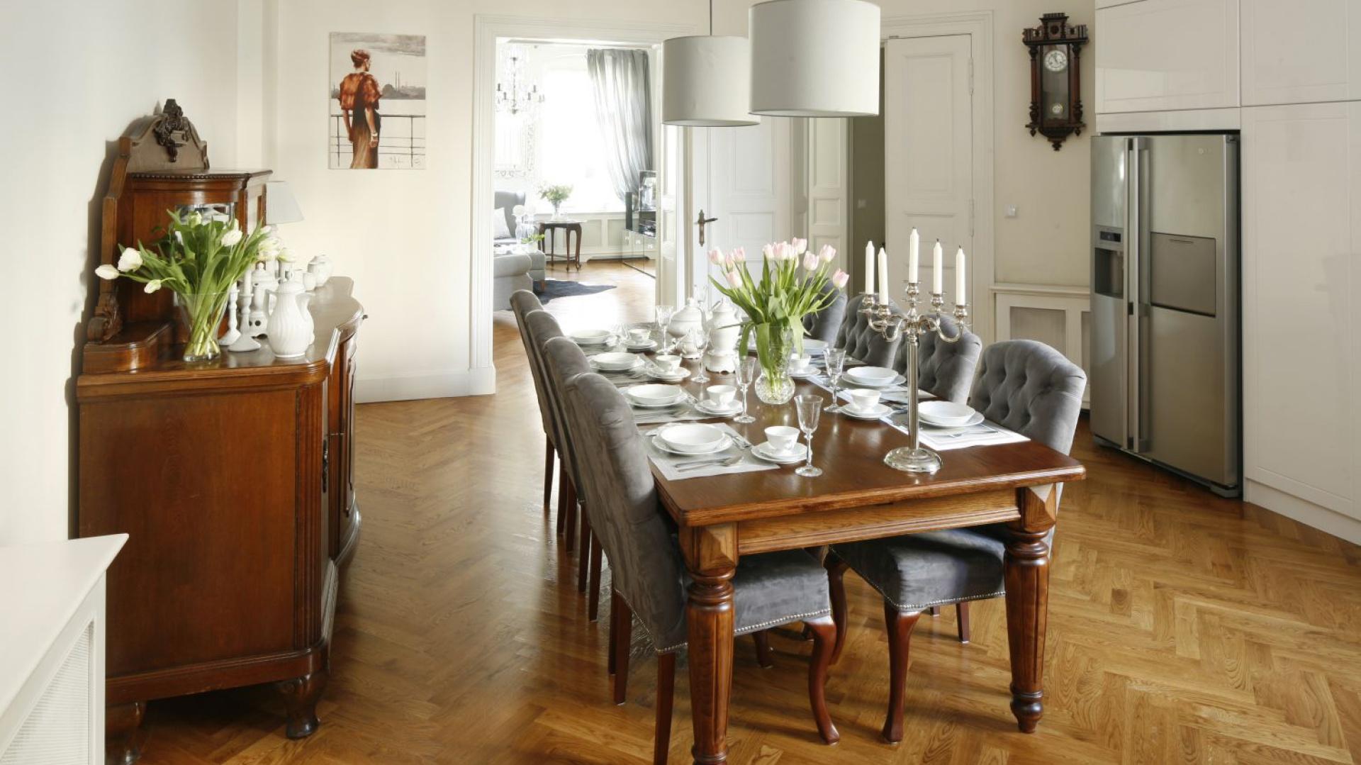 Towarzyszą mu miękkie tapicerowane krzesła których tekstylna część harmonizuje z abażurami lamp nad stołem. Projekt: Iwona Kurkowska. Fot. Bartosz Jarosz
