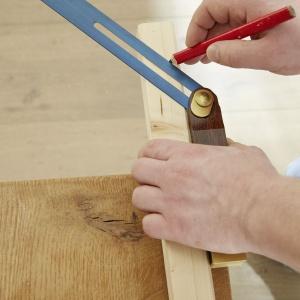 Krok 1: Na początku należy zaznaczyć, jak mają być przycięte listwy drewniane na ramę (34 x 54 mm) oraz listwy na uchwyt do rowerów (38 x 38 mm). Do wykonania ramy należy przyciąć z dwóch listew o długości 2 m cztery długie listwy poprzeczne na tył i część dolną (każda o długości 92 cm), z wąskiej listwy o długości 2,5 m dwie listwy narożne (każda o długości  78 cm) oraz dwie boczne listwy na część dolną (każda o długości 43,5 cm). Do wykonania uchwytów należy przyciąć z dwóch szerszych listew o długości 2,5 m osiem listew, każda po 57 cm, które po obu stronach muszą być ścięte pod kątem 45 stopni. Najlepiej posłużyć się przy tym kątownikiem nastawnym. Fot. Bosch