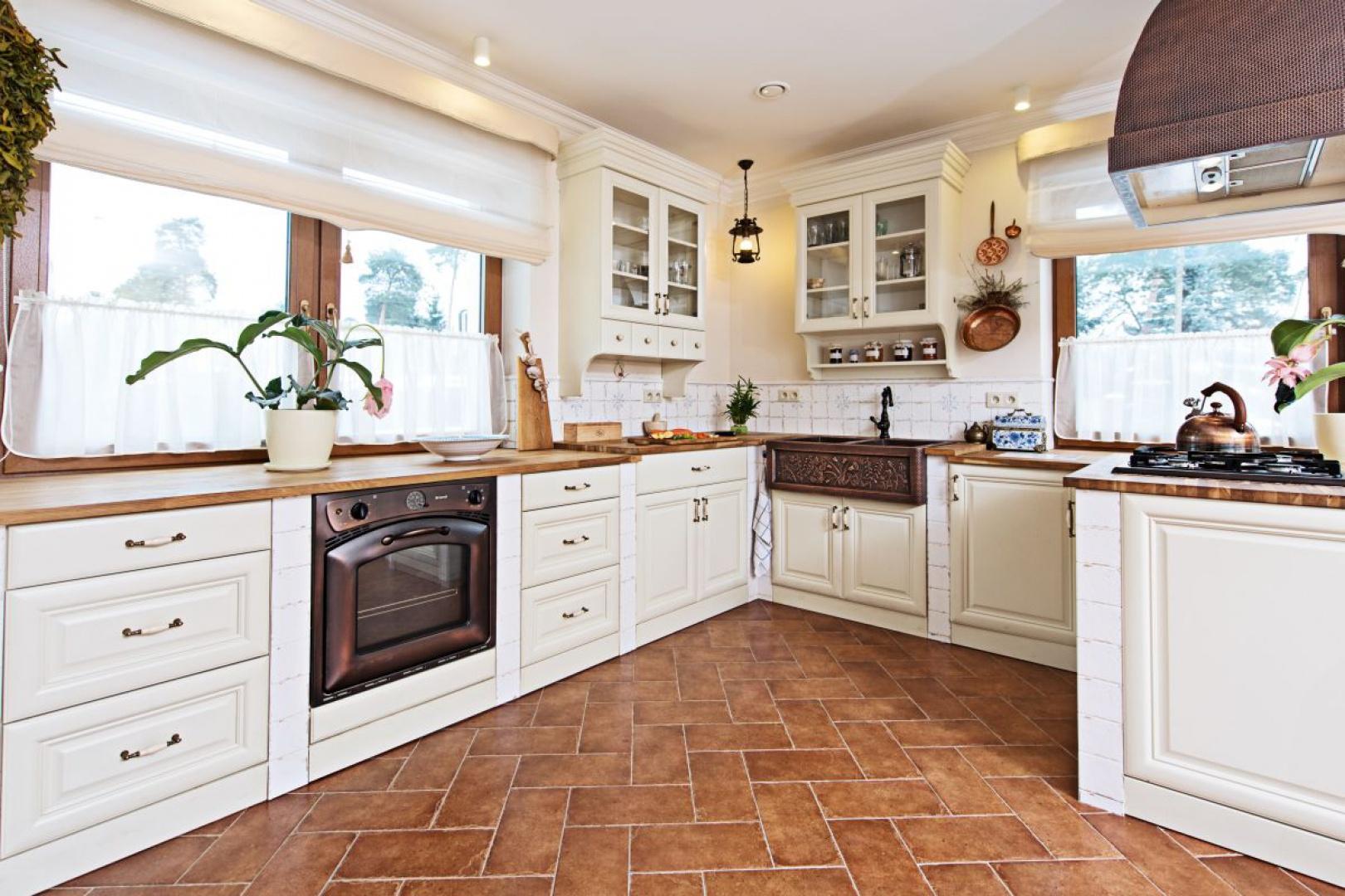 W tej kuchni jest wszystko, czego moglibyśmy oczekiwać od rustykalnej aranżacji. Frezowane fronty, drewniany blat, niezwykle zdobny metalowy okap, kuty zlewozmywak oraz delikatne tekstylia w oknach. Projekt i Fot. Kamila Paszkiewicz
