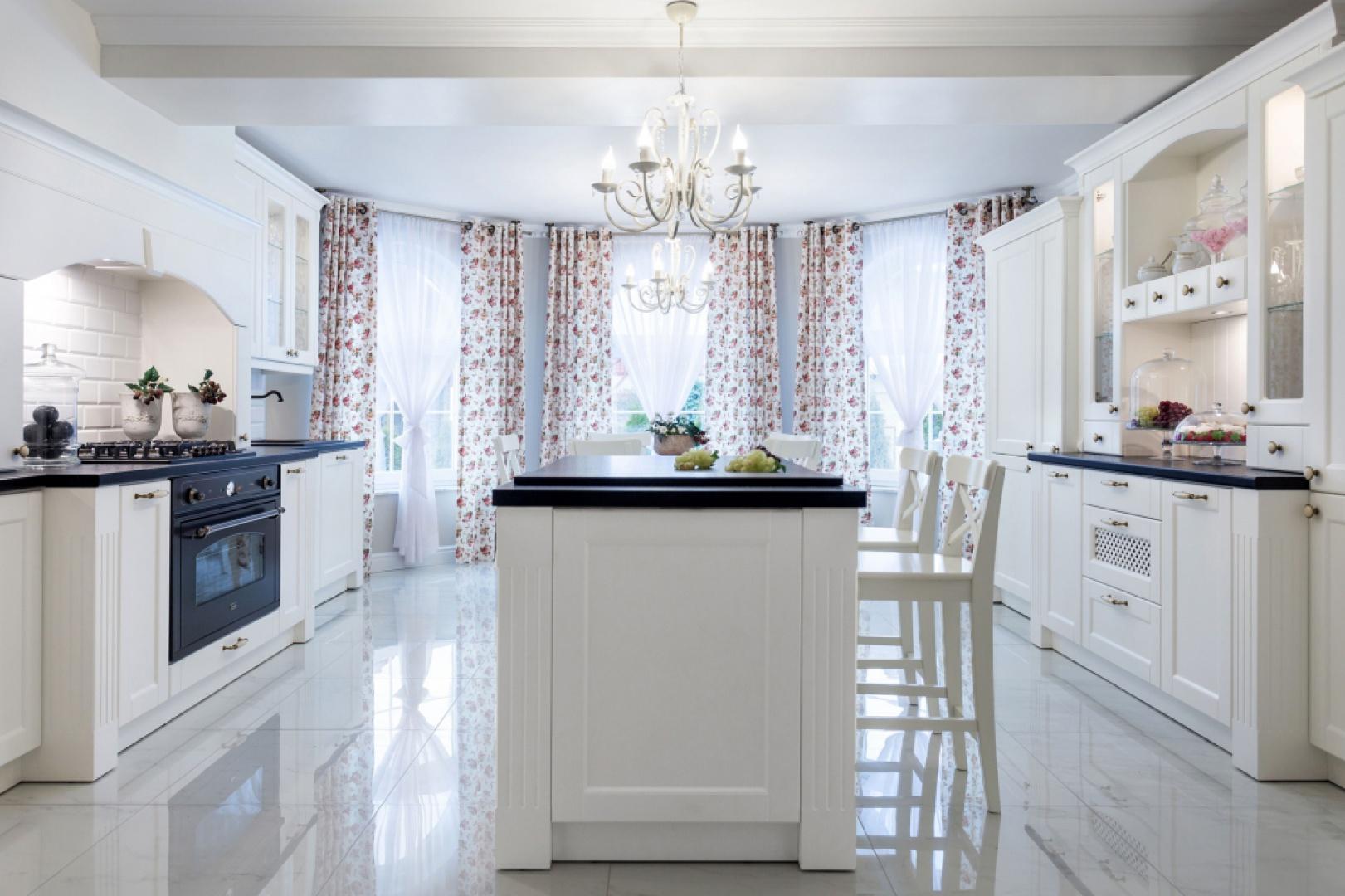 Białe kafle nad blatem, stylizowana forma zabudowy kuchennej, dekoracyjne, ażurowe panele w meblach oraz kwieciste tekstylia budują w tej kuchni rustykalną atmosferę. Projekt: Małgorzata Błaszczak. Fot. Pracownia Mebli Vigo