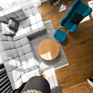 Kolorowym akcentem w salonie jest turkusowy fotel-leżanka z podnóżkiem w zestawie. Projekt: arch. Indre Sunkodiene. Fot. Leonas Garbačauskas