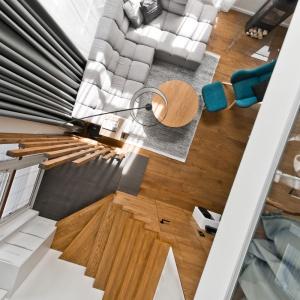 Wzdłuż bardzo wysokich okien zwisają długie zasłony układające się w plisy będące ciekawym odzwierciedleniem geometrycznych kształtów drewnianego parawanu pomiędzy salonem a holem. Projekt: arch. Indre Sunkodiene. Fot. Leonas Garbačauskas