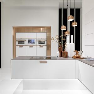 W tej kuchni biel zestawiono ze złotem. Kolor złota mają pięknie wyeksponowane na białych frontach uchwyty, tło za wysoką zabudową oraz dekoracyjne lampy nad blatem. Fot. Rational, kuchnia Topaz