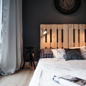 Na zagłówku wykonanym z drewnianej palety zaczepiono dwie lampki nocne o technicznej formie. Domownicy mogą sterować kierunkiem padania światła. Projekt: Marta i Michał Raca. Fot. Adam Ościłowski