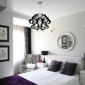 W centrum tej sypialni znalazł się imponujący dekoracyjny żyrandol w czarnym kolorze. Na szafkach nocnych stanęły lampki - również całe w czerni, ale już o znacznie bardziej oszczędnych kształtach. Projekt: Małgorzata Galewska. Fot. Bartosz Jarosz
