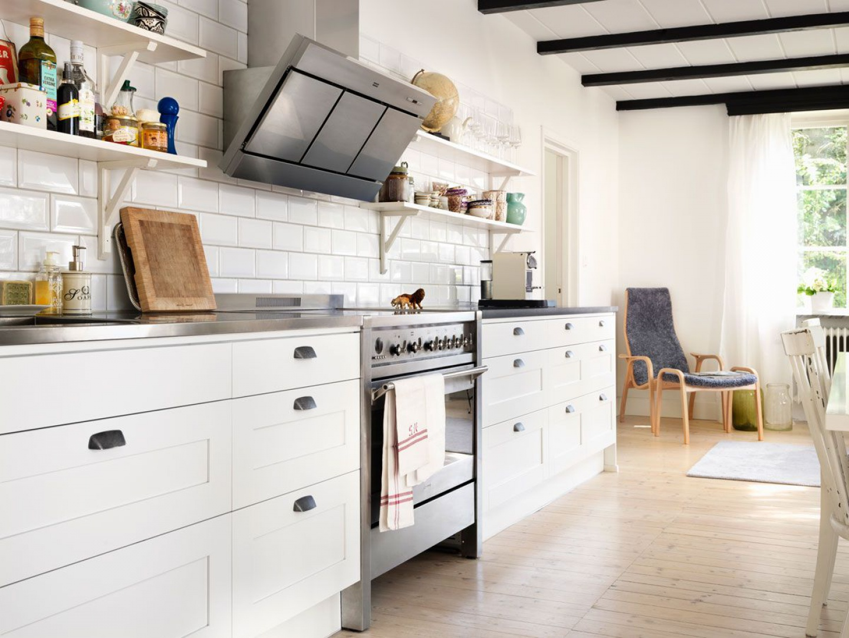 Meble kuchenne w białym kolorze idealnie wpisują się w styl skandynawski. Podobnie, jak drewniana podłoga oraz otwarte półki nad blatem. Fot. Ballingslov