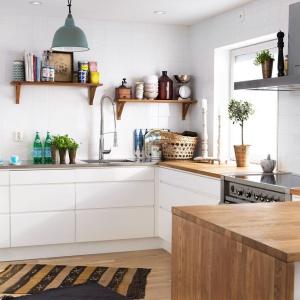Białe, proste meble są bardzo skandynawskie - podobnie jak brak tekstyliów w oknie, przez które wpada dzienne światło. Półki nad blatem służą przechowywaniu podręcznych akcesoriów. Wykonane z drewna korespondują z blatem. Fot. Ballingslov