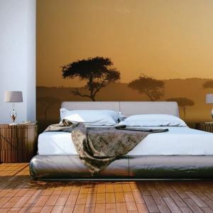 Afrykański krajobraz wkracza do przestrzeni sypialni urządzonej w kolorach ziemi za sprawą fototapety na ścianie za łóżkiem. Fot. Dekornik