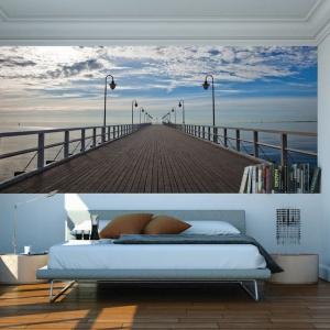 Ścianę nad łóżkiem pokryto efektowną fototapetą z pięknym widokiem na molo nad morzem. Fot. Dekornik