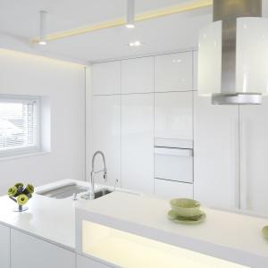 W tej nowoczesnej białej kuchni zrezygnowano z dolnej zabudowy. Całą ścianę zabudowaną pojemnymi schowkami, a strefę zmywania i gotowania przeniesiono na wyspę. Projekt: Dominik Respondek. Fot. Bartosz Jarosz