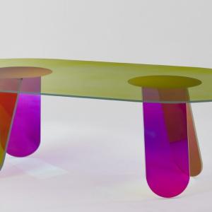 Kolekcja Shimmer powiększyła się o stoły do jadalni. Meble posiadają charakterystyczne zaokrąglone krawędzie. Modele są dostępne w wersji ze szkła transparentnego lub barwionego o charakterystycznym opalizującym wykończeniu. Jego odcień zmienia się w zależności od kąta patrzenia i padania światła. W skład kolekcji wchodzi również: wisząca półka, stoliki kawowe, konsola i lustra. Projekt: Patricia Urquiola. Fot. Glas Italia