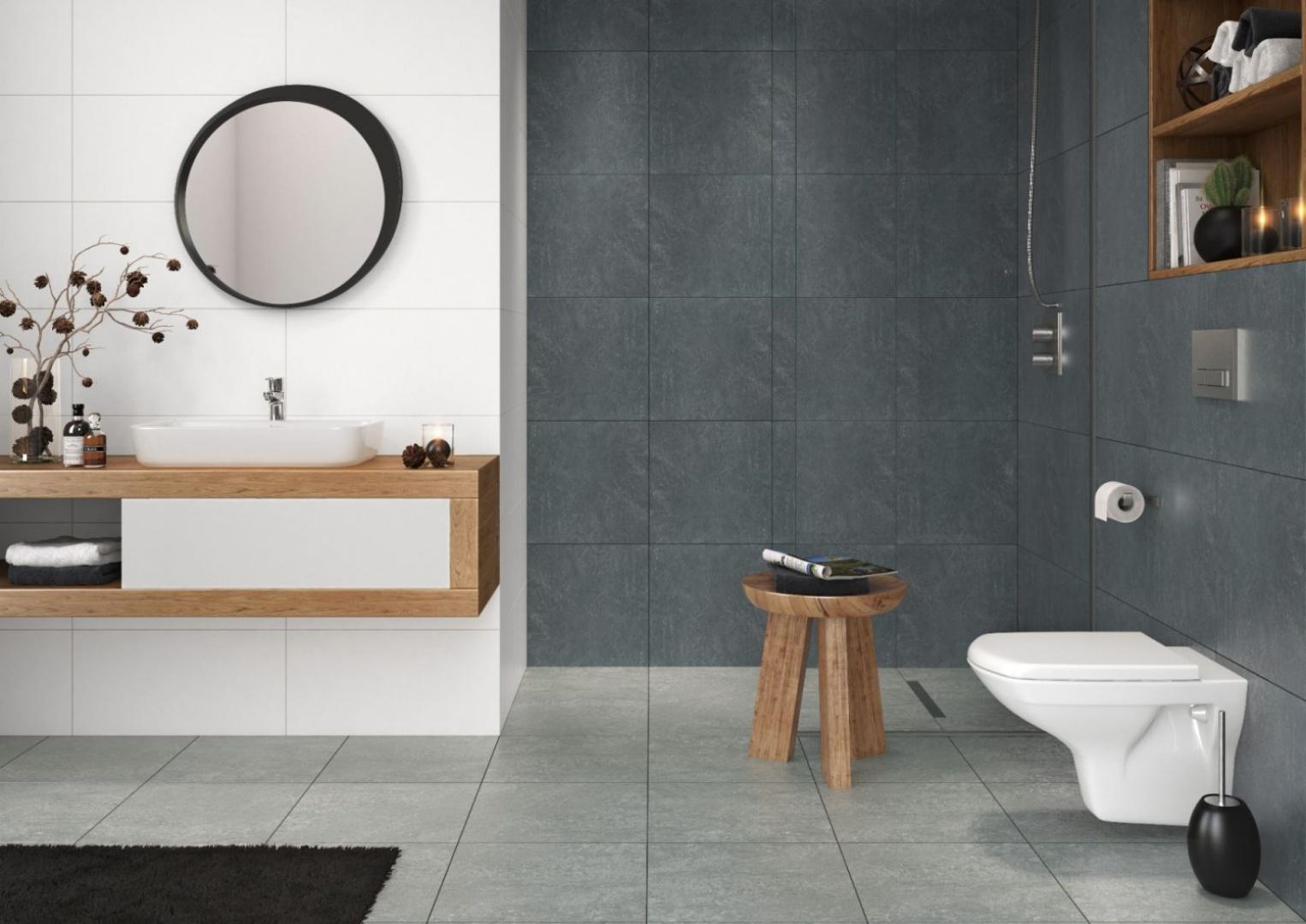 Aranżacja łazienki stworzona przez producenta płytek ceramicznych. Z szarymi gresami i nowoczesną stylistyką idealnie komponuje się okrągłe lustro w asymetrycznej ramie. Fot. Cersanit