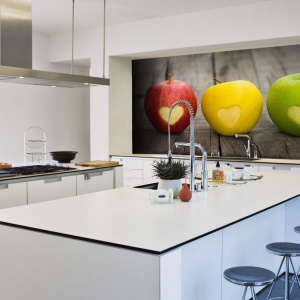 Fototapeta z kolorowymi jabłuszkami, na którym wydrążono urocze serduszka zdecydowanie dodaje charaktery nowoczesnej, ale dosyć niewyraźnej aranżacji białej kuchni. Fot. Picassi