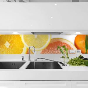 Fototapeta nad blatem, której motywem są soczyste cytrusy sprawiła, że biała kuchnia stała się żywsza. Motyw orzeźwiających owoców dodaje energii. Fot. Decomania